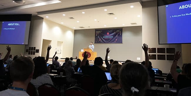 People raise their hands during the opening announcements of WordCamp Asheville 2018