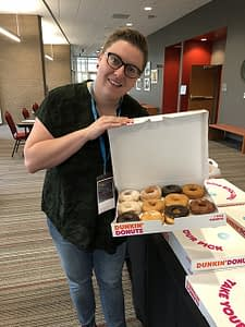A woman holds open a box of donuts